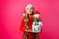 Девочка-подросток нося шляпу и сусаль Санты на шеи держа Христос стоковая фотография rf