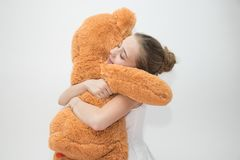 Девочка-подросток обнимая плюшевый медвежонка стоковые фотографии rf