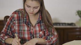 Девочка-подросток портрета милый делая ее домашнюю работу сидя дома на таблице Школьница перезаписывая текст от видеоматериал