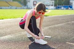 Девочка-подросток связывая шнурки идущих ботинок перед тренировкой Стоковая Фотография