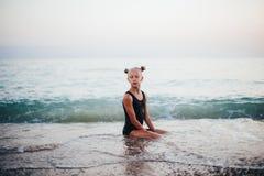 Девочка-подросток сидит на пляже в черном купальнике стоковые фото