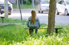 Девочка-подросток сидит на стенде около дерева в дворе дома стоковая фотография rf