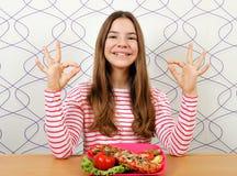 Девочка-подросток с сэндвичем и в порядке знаком руки стоковые фото