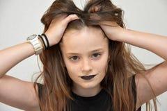 Девочка-подросток с черными губами tousles ее волосы стоковая фотография