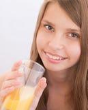Девочка-подростки выпивая апельсиновый сок Стоковые Изображения