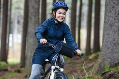 Девочка-подросток велосипед на тропках леса Стоковое фото RF
