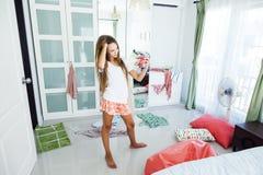 Девочка-подросток выбирая одежду в шкафе Стоковые Изображения
