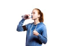 Девочка-подросток выпивая от бутылки с водой Изолированная съемка студии Стоковое фото RF