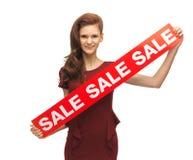 Девочка-подросток в красном платье с знаком продажи Стоковые Фотографии RF