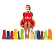 Девочка-подросток в красном платье с хозяйственными сумками Стоковые Изображения RF