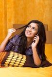 Девочка-подросток говоря на ее умном телефоне лежа на кровати Стоковое Фото