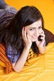 Девочка-подросток говоря на ее умном телефоне лежа на кровати Стоковые Изображения RF