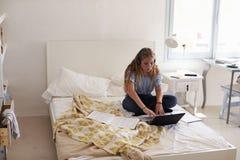 Девочка-подросток делая домашнюю работу сидя на ее кровати с компьтер-книжкой Стоковое Изображение