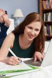 Девочка-подросток используя компьтер-книжку для того чтобы сделать домашнюю работу в спальне Стоковое Фото
