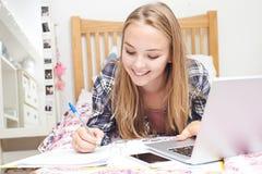 Девочка-подросток используя компьтер-книжку для того чтобы сделать домашнюю работу в спальне Стоковые Фотографии RF