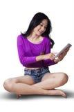 Девочка-подросток используя таблетку в студии Стоковая Фотография RF