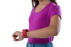 Девочка-подросток используя smartwatch против белой предпосылки Стоковое Изображение