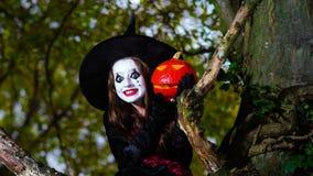 Девочка-подросток одел в костюме ведьмы сидя на дереве Стоковая Фотография RF