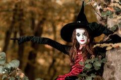 Девочка-подросток одел в костюме ведьмы сидя на дереве Стоковое Изображение RF