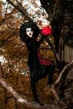 Девочка-подросток одел в костюме ведьмы сидя на дереве Стоковое Фото