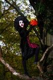 Девочка-подросток одел в костюме ведьмы сидя на дереве Стоковая Фотография