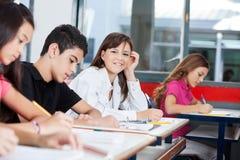 Девочка-подросток при друзья писать на столе Стоковые Фото