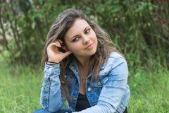 Девочка-подросток сидит в траве Стоковые Фото