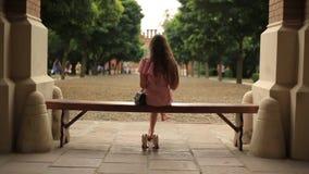 Девочка-подросток сидя вниз на стенде в природе и читая книгу barefoot при пересеченные ноги задний взгляд видеоматериал