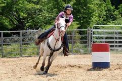 Девочка-подросток скакать вокруг поворота в гонке бочонка Стоковая Фотография