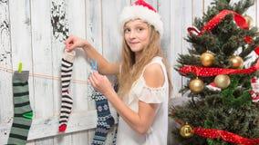 Девочка-подросток смотря в носки Нового Года и рождества Стоковое Изображение RF