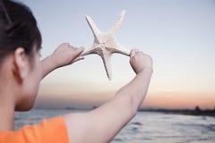 Девочка-подросток смотря и задерживая морские звёзды Стоковое Фото