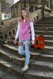 Девочка-подросток с гитарой идя вниз с старых каменных лестниц в парке Стоковые Фотографии RF