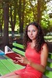 Девочка-подросток с книгой чтения вьющиеся волосы Стоковое фото RF