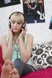 Девочка-подросток слушая к музыке на наушниках в кровати Стоковое Фото