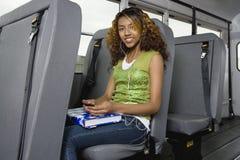Девочка-подросток слушая к mp3 плэйер на шине Стоковое Изображение RF