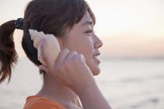 Девочка-подросток слушая к seashell, профилю Стоковые Фотографии RF