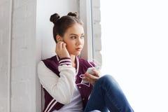 Девочка-подросток с smartphone и наушниками Стоковое фото RF