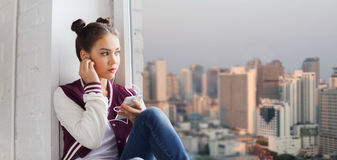 Девочка-подросток с smartphone и наушниками Стоковые Изображения