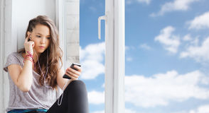Девочка-подросток с smartphone и наушниками Стоковое Фото