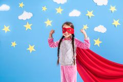 6 девушек года белокурых одела как супергерой имея потеху дома Оягнитесь на предпосылке яркой голубой стены Стоковое Изображение