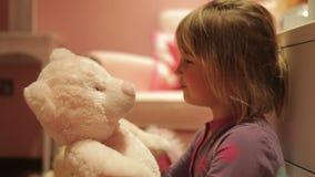 Девушка давая объятие плюшевого медвежонка пока носящ пижамы видеоматериал
