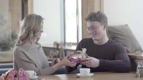 Девушка дает ее парню подарок в коробке с лентой акции видеоматериалы