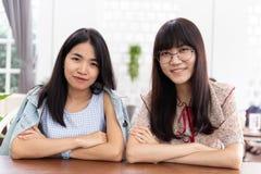 Девушка 2 азиатов предназначенная для подростков сидящ совместно взгляд и улыбка Стоковое фото RF