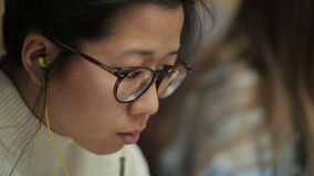 Девушка азиатских стекел и наушников появления у в ушах читает видеоматериал