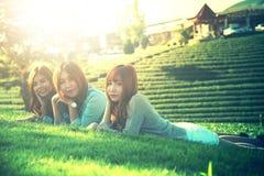 Девушка 3 Азия лежа на зеленой траве на ферме чая Стоковая Фотография