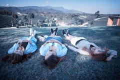 Девушка 3 Азия лежа на зеленой траве на ферме чая Стоковые Изображения