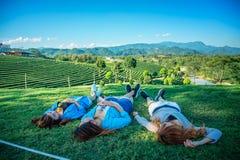 Девушка 3 Азия лежа на зеленой траве на ферме чая Стоковые Изображения RF