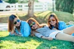 Девушка 3 Азия лежа на зеленой траве на ферме чая Стоковое Изображение RF
