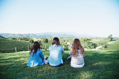 Девушка 3 Азия сидит на зеленой траве на кафе на открытом воздухе Стоковые Фото