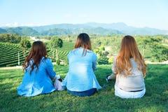Девушка 3 Азия сидит на зеленой траве на кафе на открытом воздухе Стоковое Фото